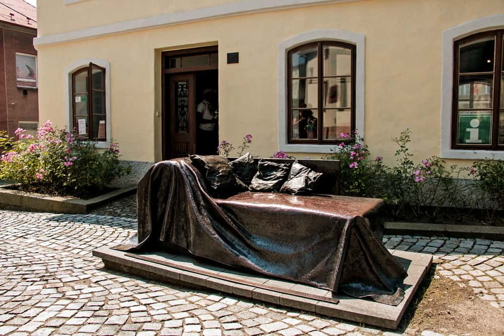 A bronze couch in front of an old house