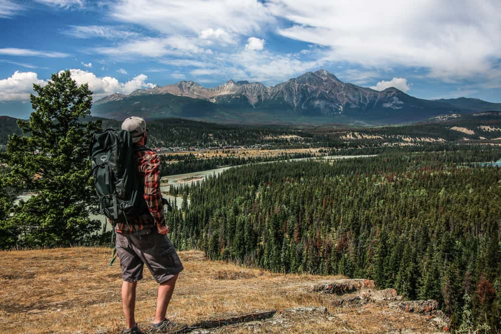 Man standing on a cliff overlooking mountains, wearing a large backpack.