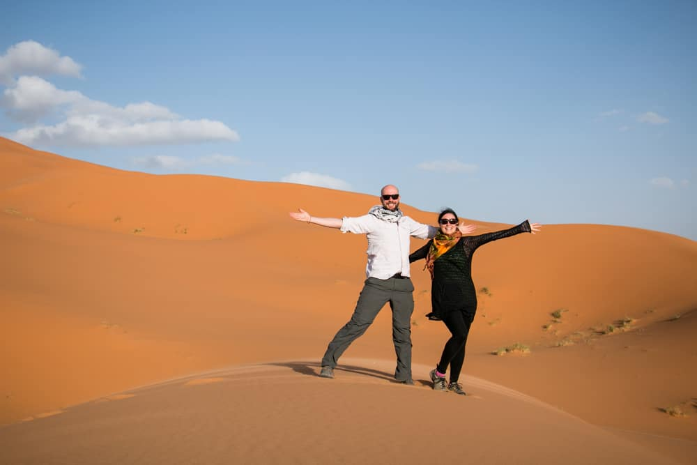 Man and woman standing in the desert as wind blows sand.