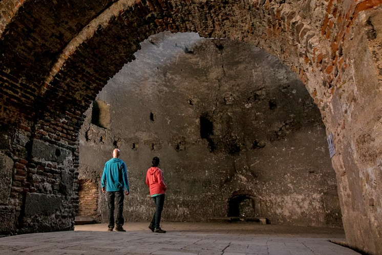 Two people in a stone room, both wearing bright coloured Prana brand hoodies.