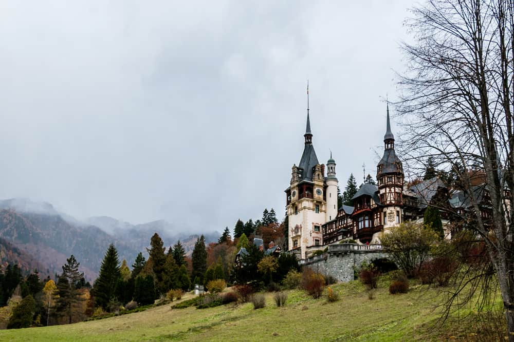 A white and blue castle in a green hill in Romania