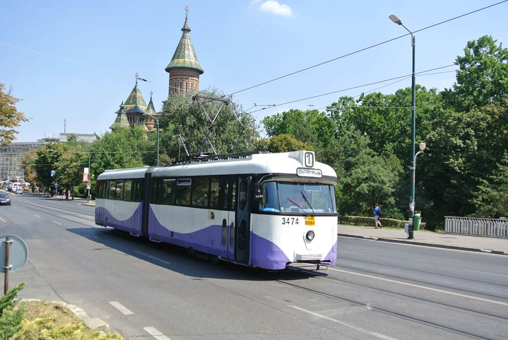 A white and purple tram along a paved road with tracks