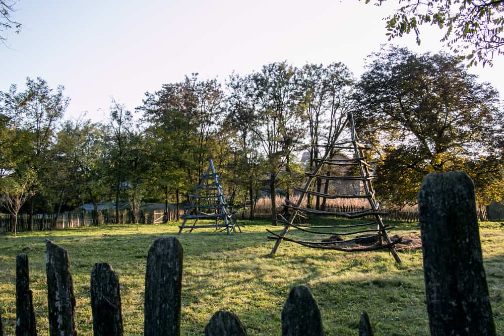 An old wooden fence surrounds a Romanian yard with grass-drying stands