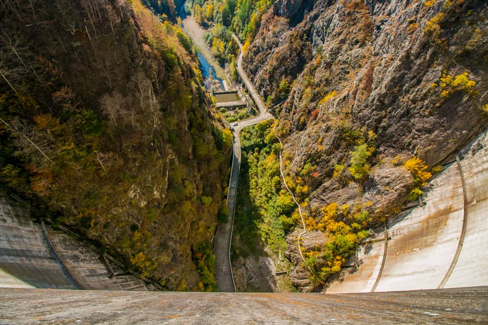 Looking down the side of a large dam in Romania with colourful yellow and orange trees