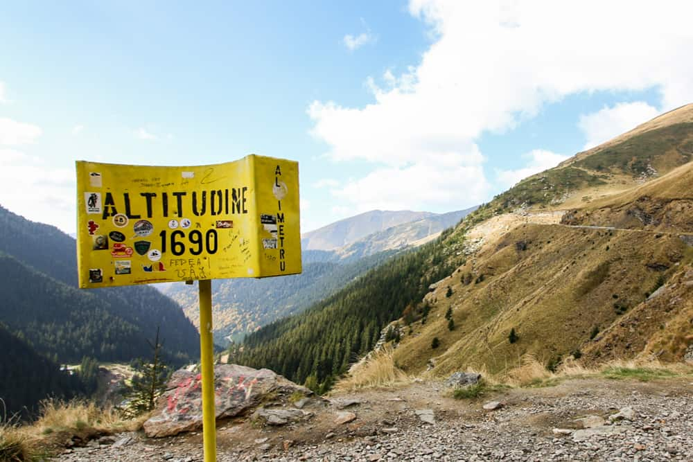 A yellow sign overlooking a valley, noting 1690m altitude of the Transfagarasan highway