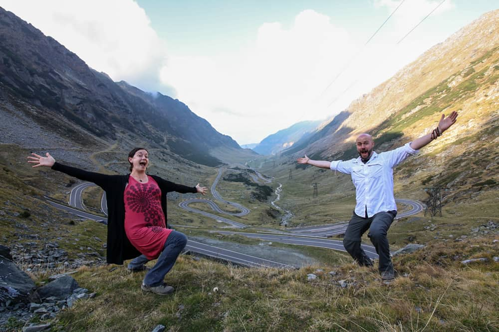 Two people posing over the Transfagarasan highway in Romania