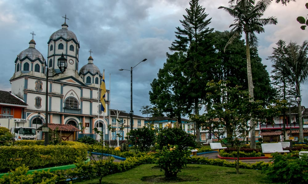 Colombia: Colourful town square with a colonial church under grey clouds.