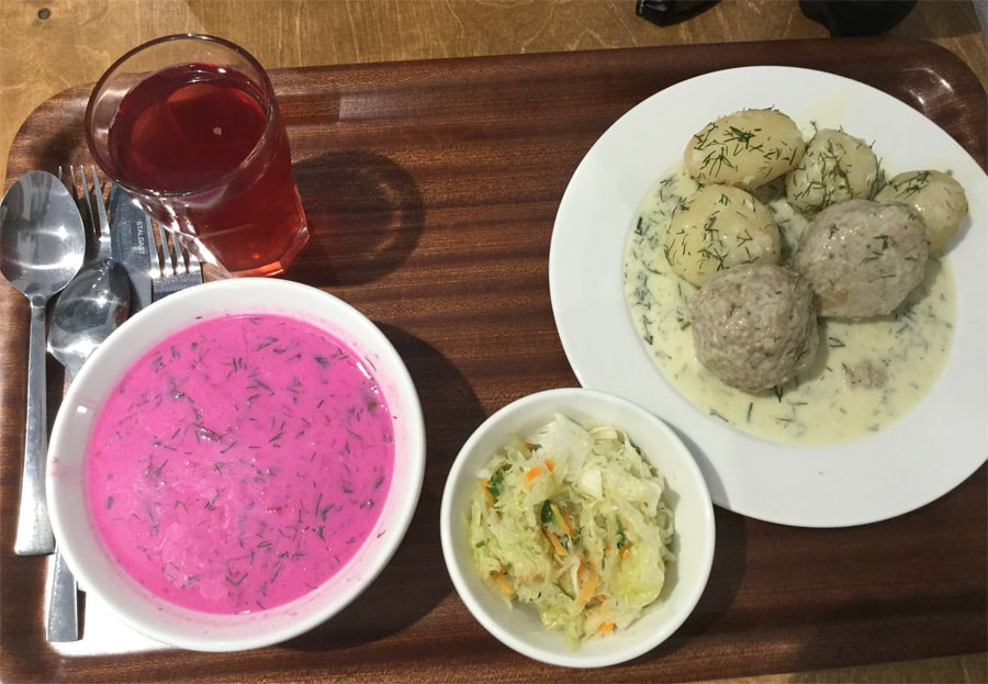 A bowl of pink soup, some salad, and a plate of meatballs with potatoes