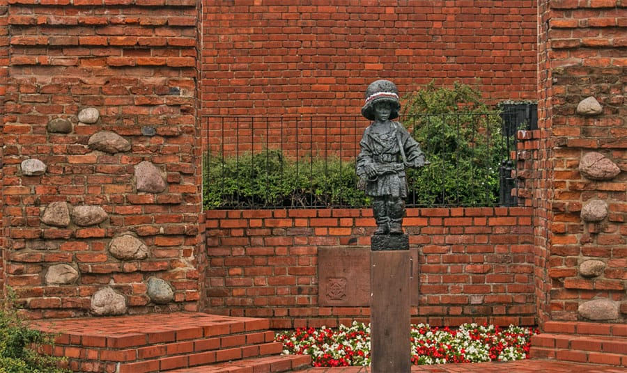 A red brick wall with a statue of a child soldier in front