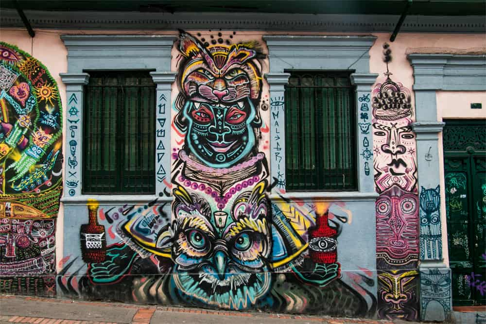 Very colourful graffiti with tribal images and a totem pole