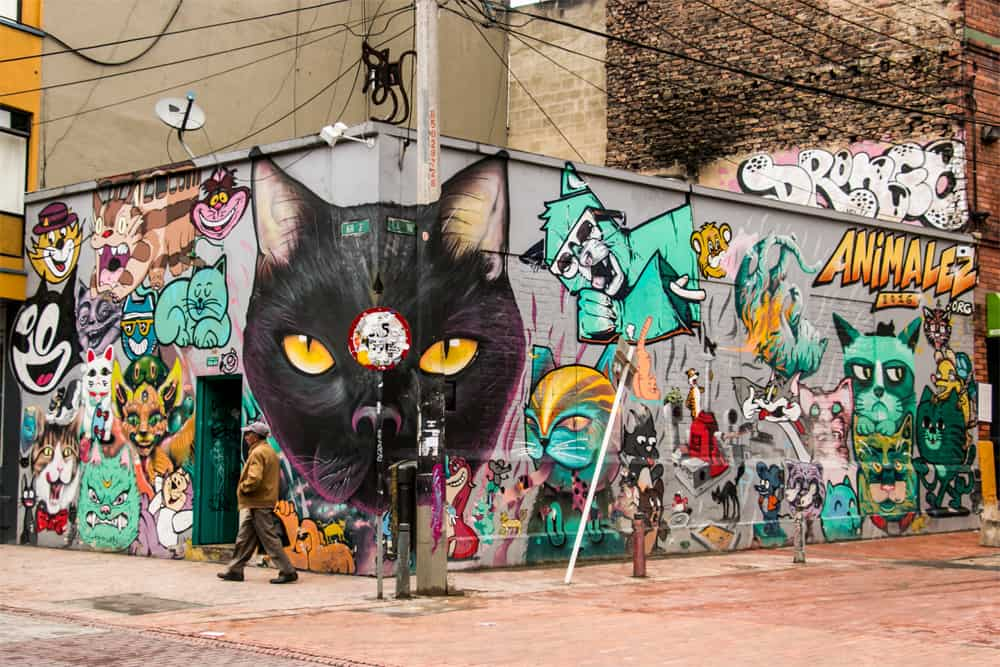 "Bogota Graffiti Tour Cat"" alt=""Graffiti of different cartoon cats on a wall. One of the cats is partially painted on a light pole that would otherwise block the mural."