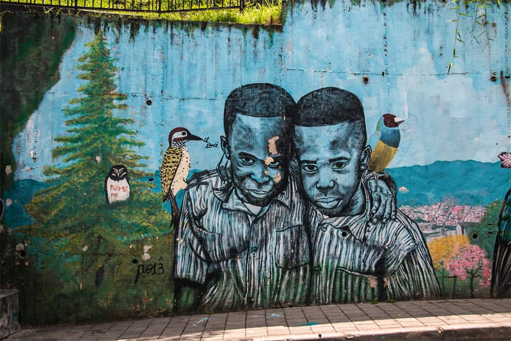 A blue wall with the graffiti of two boys hugging. Birds sit on their shoulders.