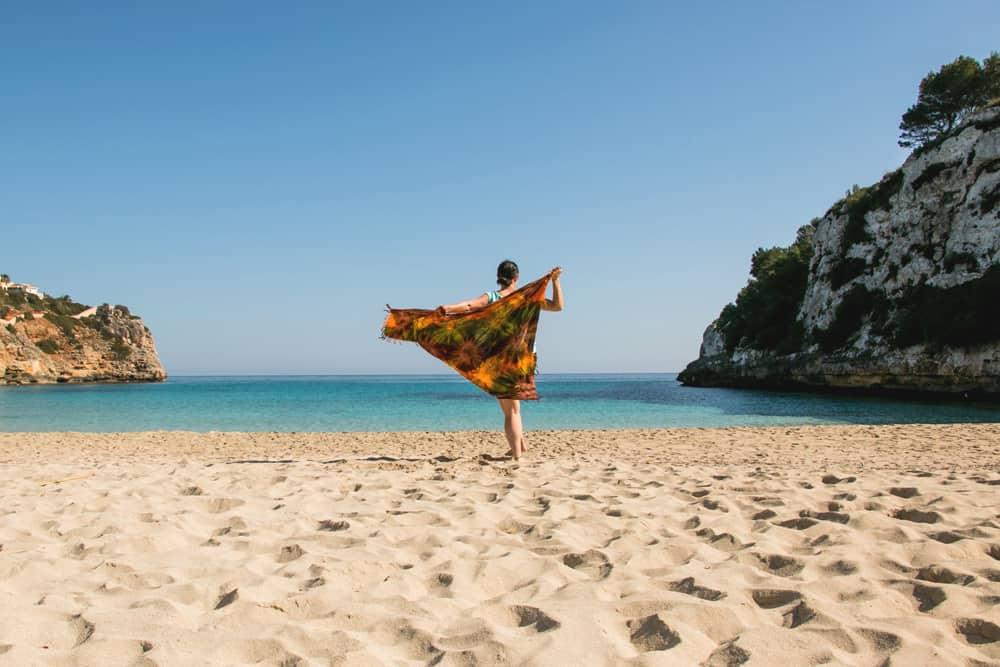 A woman on a beach with an orange sarong