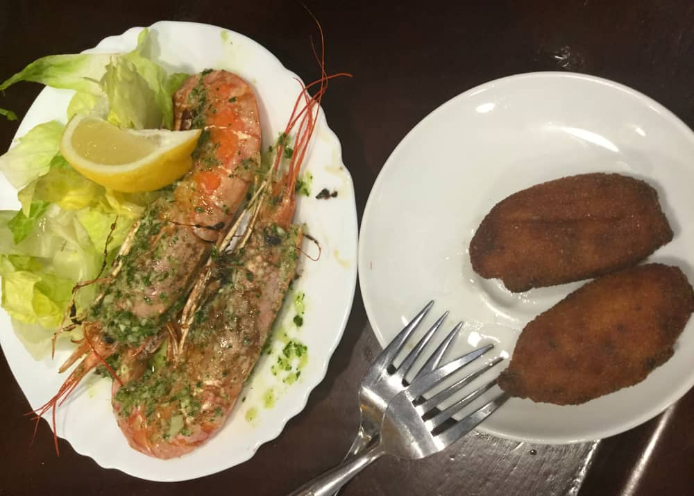 Grilled prawns and potato croquettes in a tapas restaurant in Barcelona.