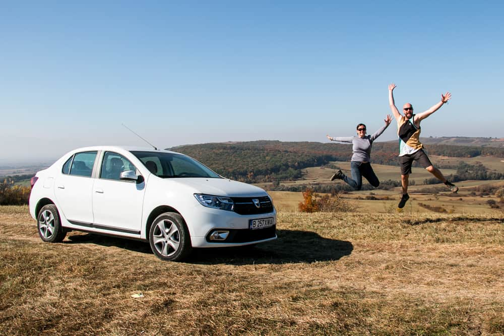 Two people jumping beside a car in Romania with a field and hills in the background