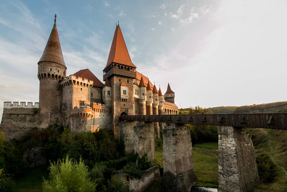 Corvin Castle, a large castle in Hunedoara Romania. Red tops on the towers and a long bridge to the gate.