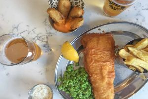 Fish and chips on a plate with peas