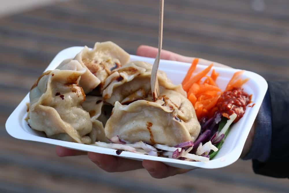 Foam plate with several Tibetan momo dumplings and sauce.