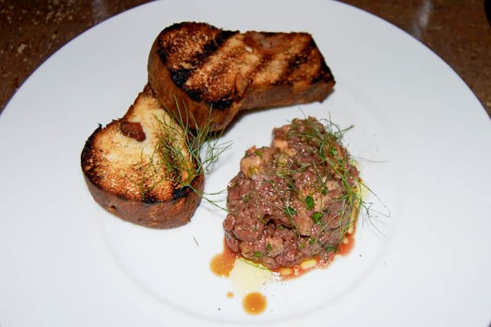 A plate with toast and a small pile of chopped meat.