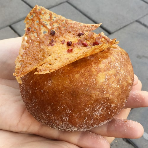Sourdough doughnut from Pinkmans bakery. A round ball of fried dough topped with a crispy garnish.