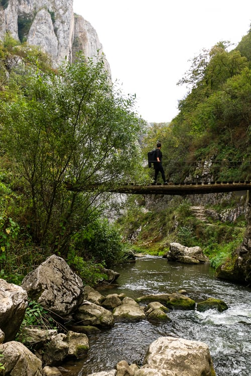 Kylee standing on a wooden bridge over a stream in Turda Gorge