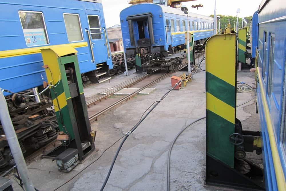 Blue train cars at the Romania Moldova border lifted by jacks off the tracks.