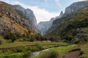 Large rocky gorge with a stream flowing from it through a green field in Romania.