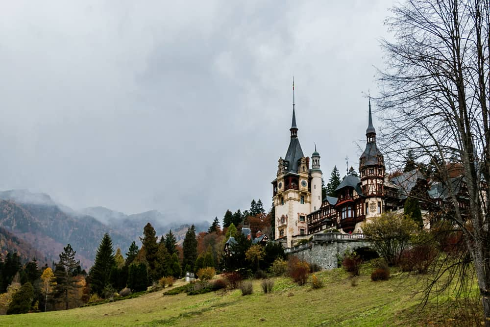 A white and brown Peles Castle on a green hillside, mountains in the background.