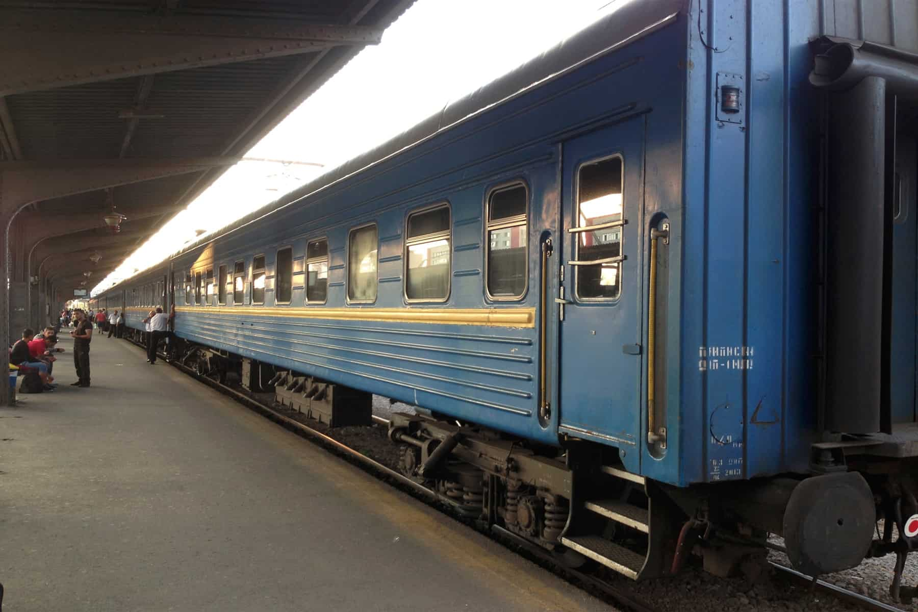 Blue train car sits beside the Bucharest train platform.