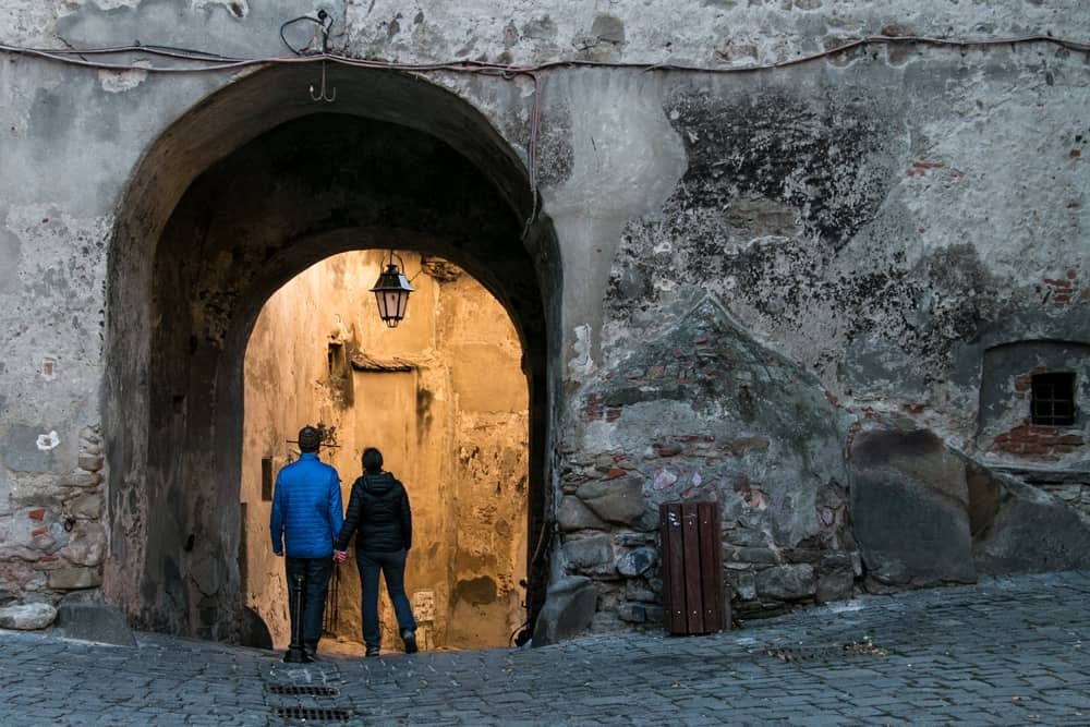 Two people walk through an archway made of stone.