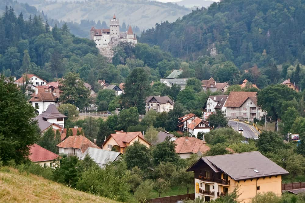 A green valley in Bran Romania with several houses and a large castle in the background