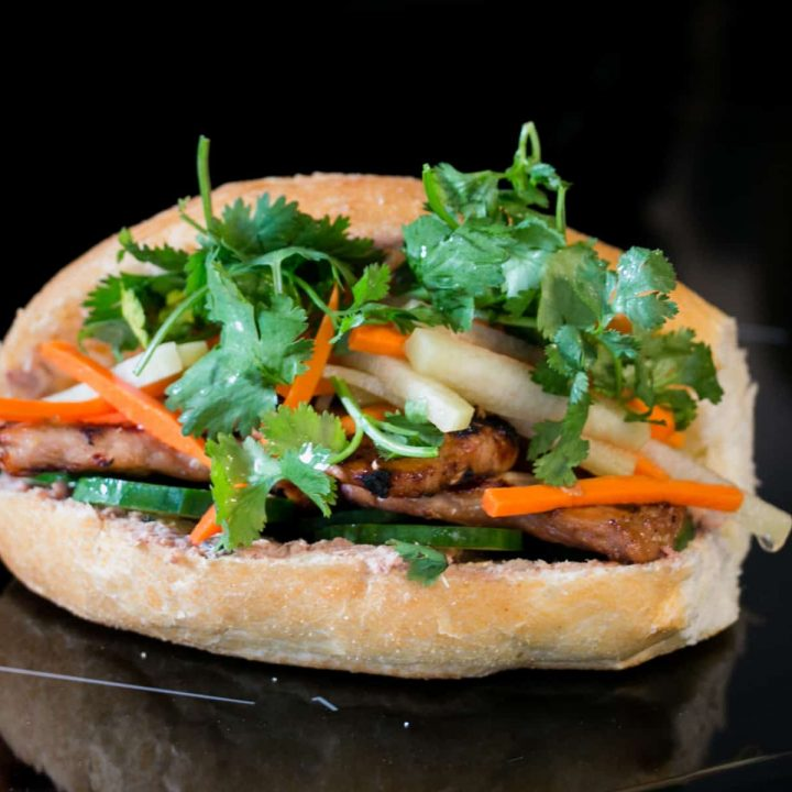 Banh Mi, a Vietnamese sandwich. A bun filled with grilled chicken, cucumber, pickled vegetables and green cilantro.