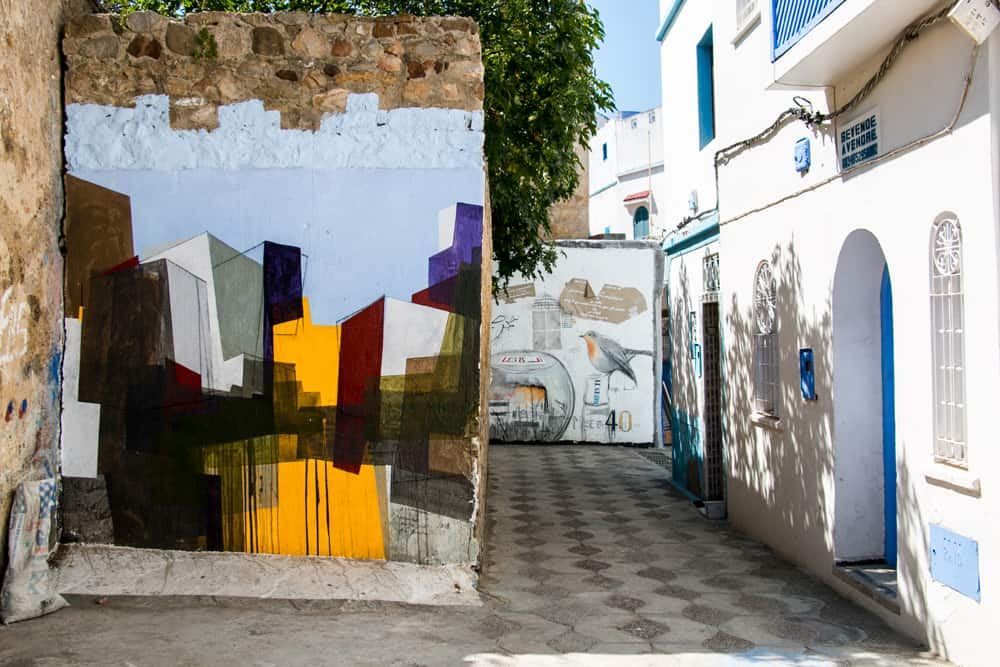 Colourful street art on a stone wall in Asilah Morocco