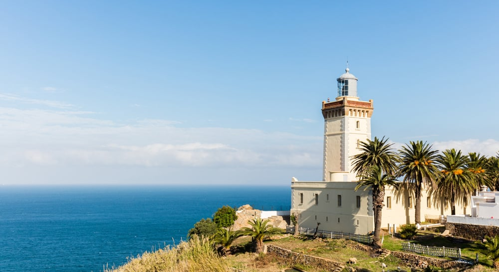 A white lighthouse surrounded by a fortified wall overlooking the Mediterranean at Cape Spartel