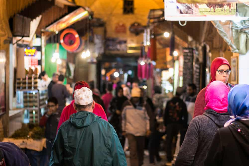 A small street at night crowded with people wearing colourful clothing