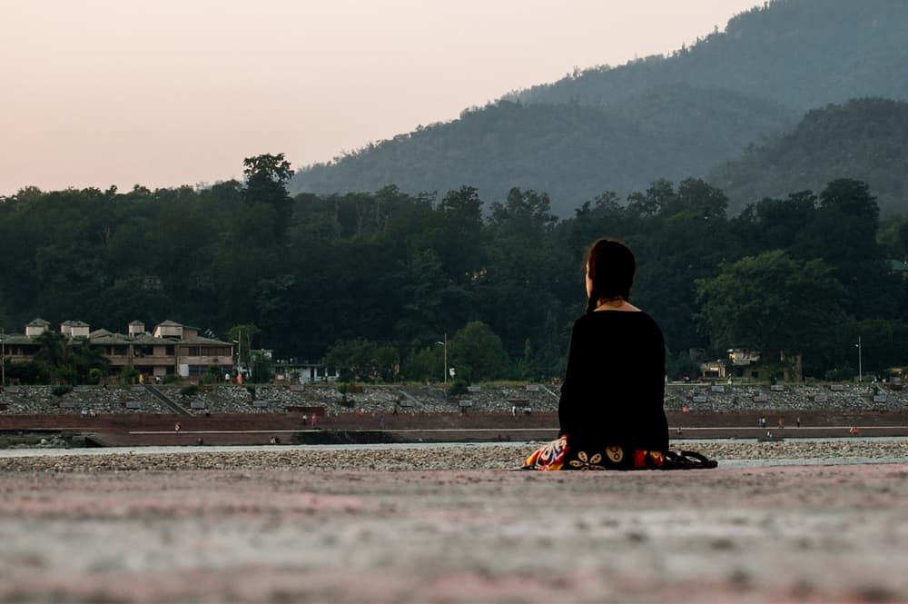 Kylee sitting on the ground near the Ganges in India
