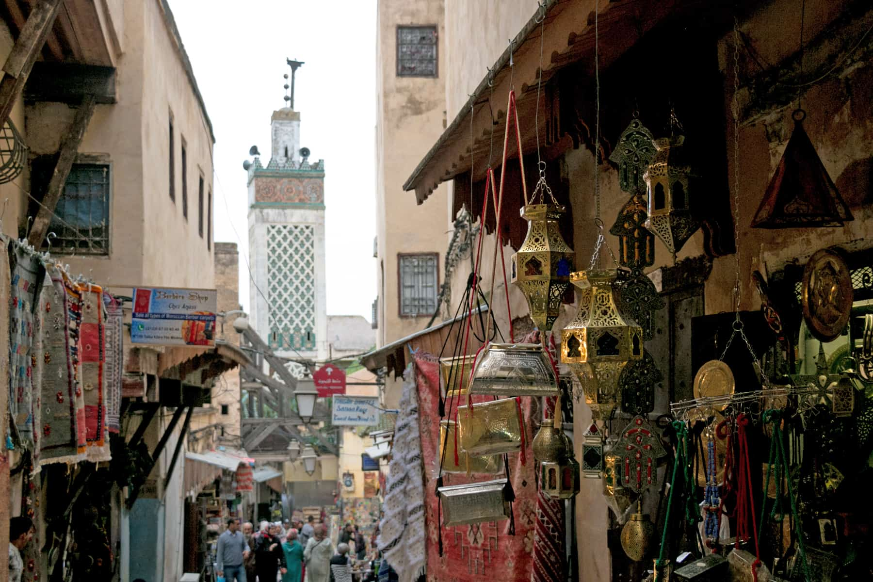 A busy street in Fes Morocco, with the minaret of a Mosque in the background