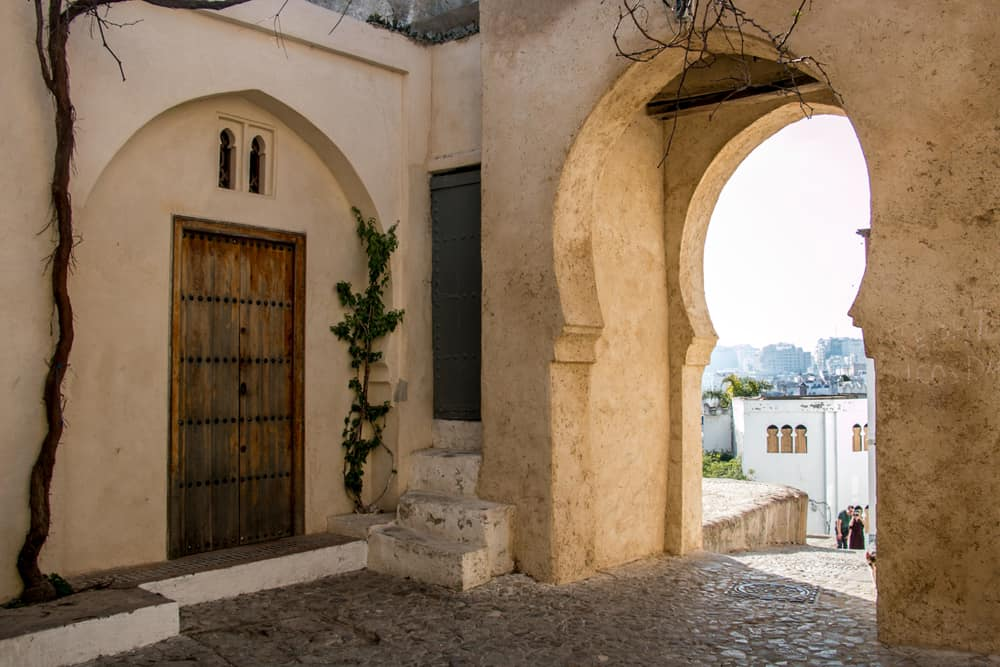 An archway in a stone wall overlooking Tangier Morocco.