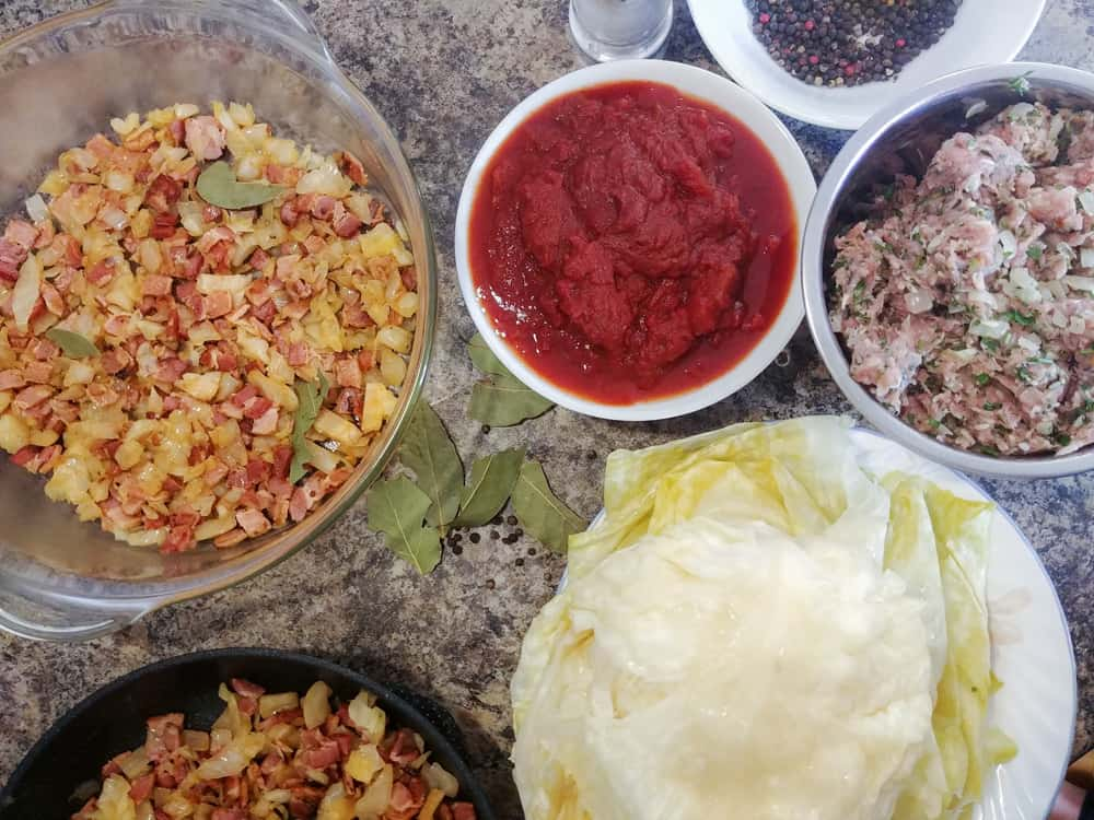 Several bowls of ingredients including sour cabbage, tomato puree, pork and bacon