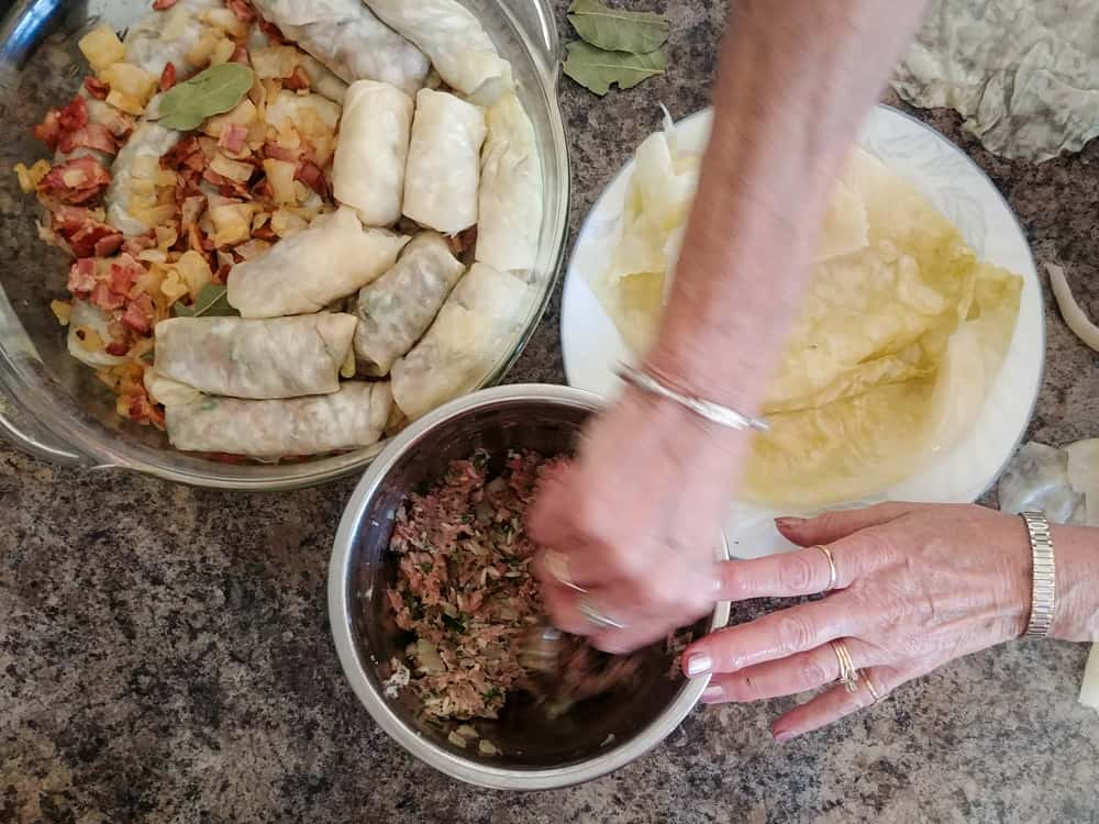 Two hands mixing together filling for cabbage rolls