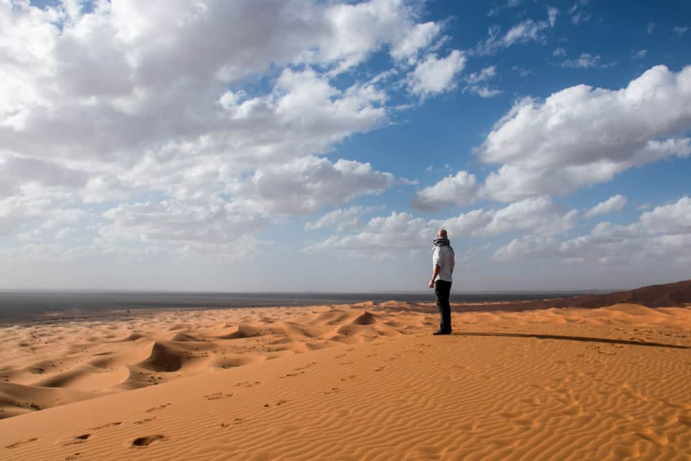 A man stands on the edge of a sand dune and looks over the desert