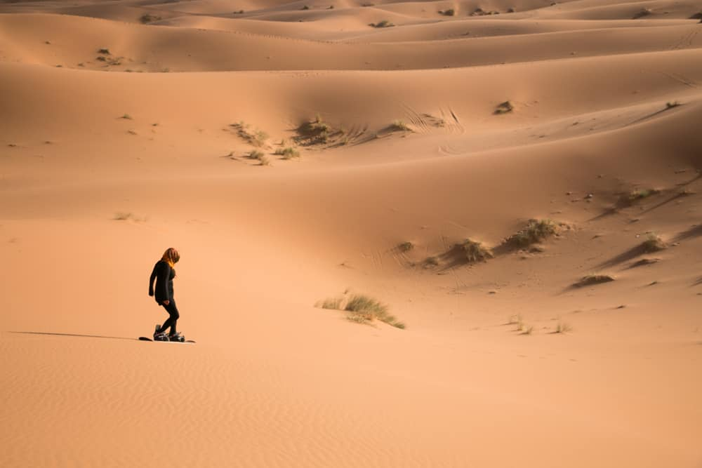 A girl riding a snowboard down the side of a sand dune