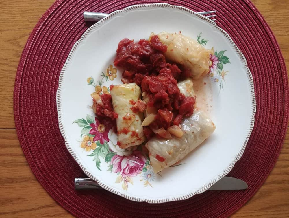A plate of cabbage rolls with tomato sauce on top.