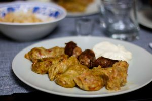 Plate of cabbage rolls with sausage and sour cream.