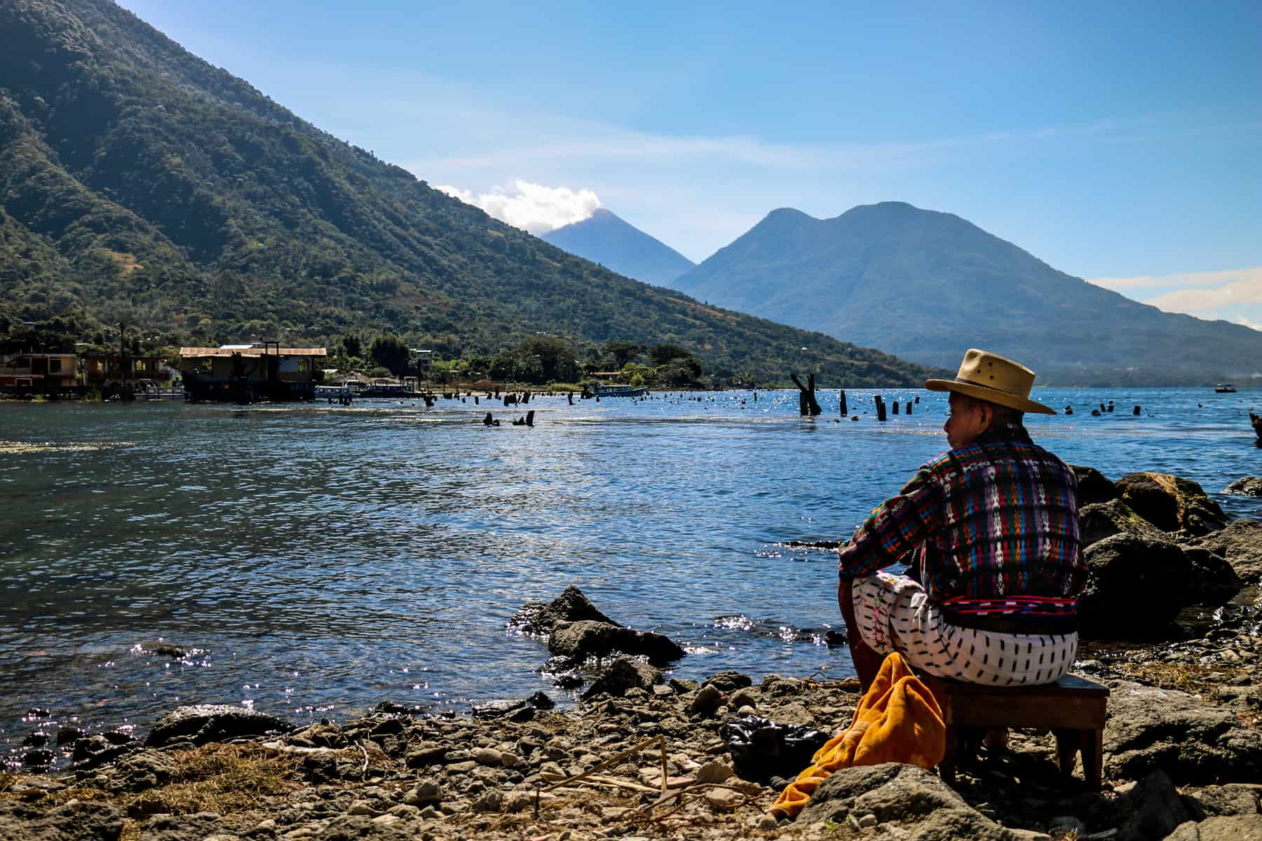 Man sits by a lake with two volcanoes in the background at Lake Atitlan, Guatemala