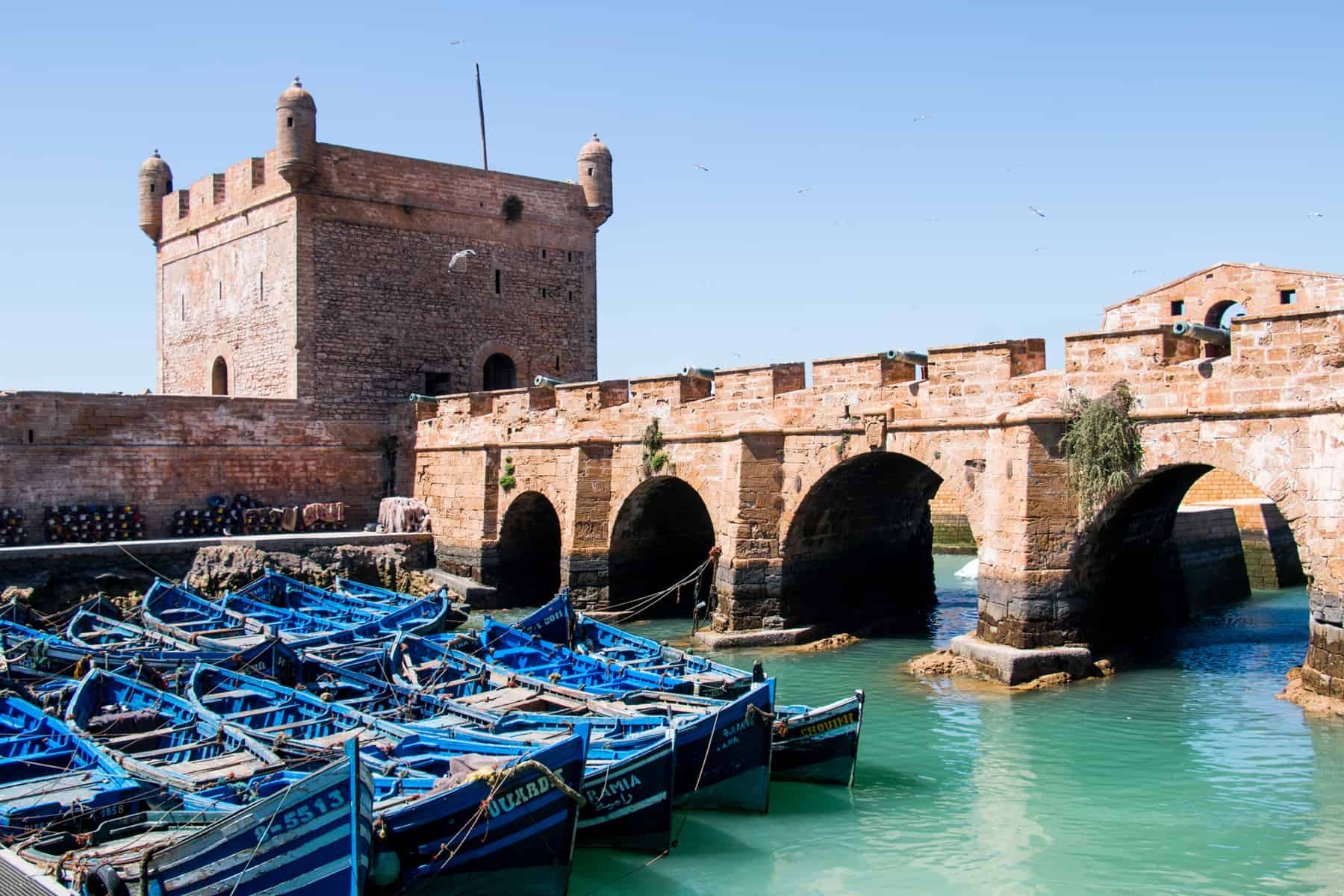 Blue boats with a stone bridge and tower on the coastal city of Essouira. There are so many fantastic restaurants in Essaouira Morocco.
