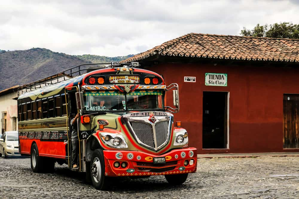 Red school bus with chrome and colourful decals beside a red building.
