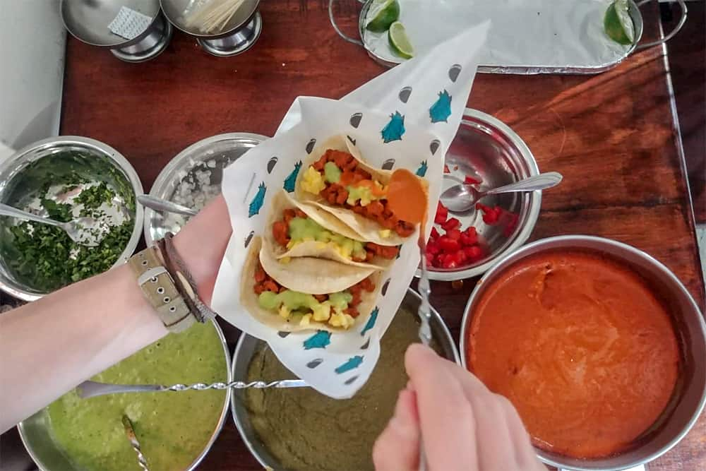 Hands holding a plate of tacos and topping them with sauces from bowls below. The best tacos in Antigua.