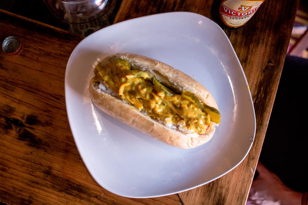 Plate with a hotdog in the centre, topped with pickles, onions and a yellow sauce.
