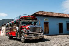 Red bus with flashy decals and stickers passing a blue building. This is one of the buses that can take you from Antigua to Panajachel